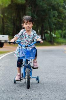 어린이 소녀는 도로에 자전거를 타고 있습니다