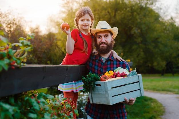 Маленькая девочка детей держа отца корзина свежих органических овощей с домашним садом.