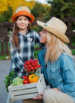 Children little girl holding mom a basket of fresh organic vegetables with home garden