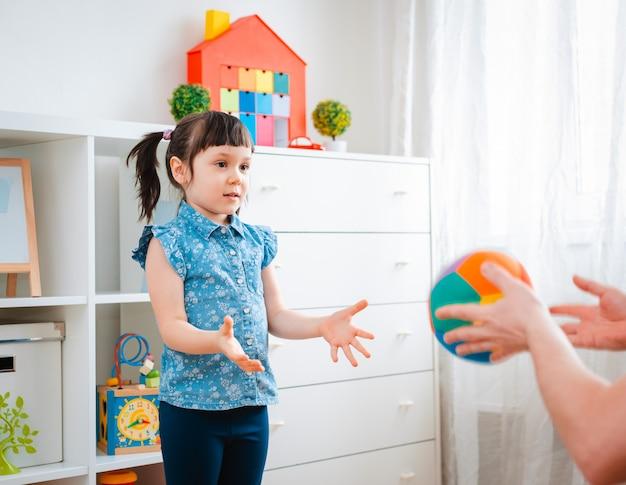 子供の小さな女の子が子供のゲーム部屋でボールを投げる