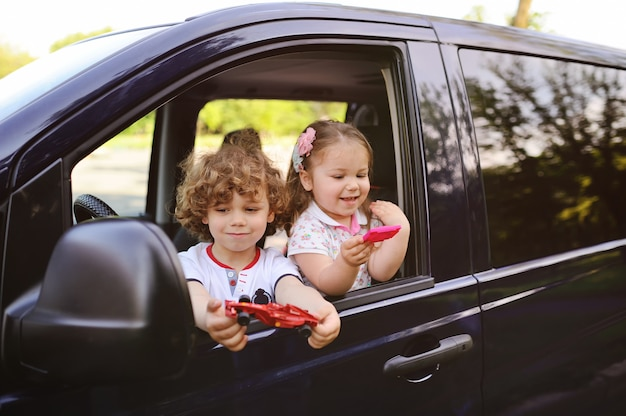 Children look out from a car window