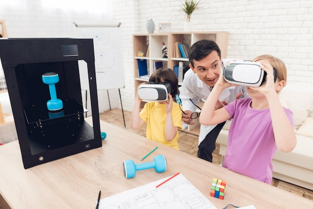 Children look at the virtual reality glasses during class.