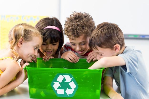 リサイクルボックスでペットボトルを見ている子供
