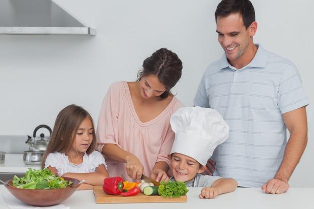 Дети смотрят на свою мать, которая режет овощи