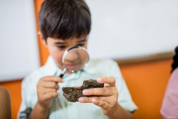 돋보기로 화석을 찾는 아이들