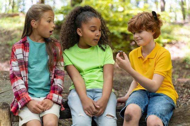 Дети вместе смотрят на улитку