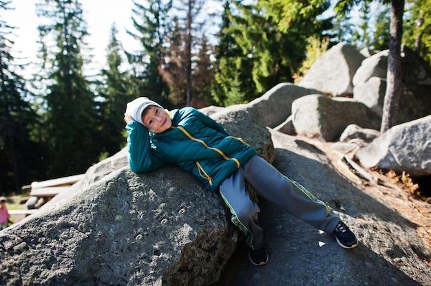 山の中で美しい日に横たわり、岩の上で休んで、山頂の素晴らしい景色を眺める子供たち。子供とのアクティブな家族の休暇の余暇。屋外の楽しさと健康的な活動。