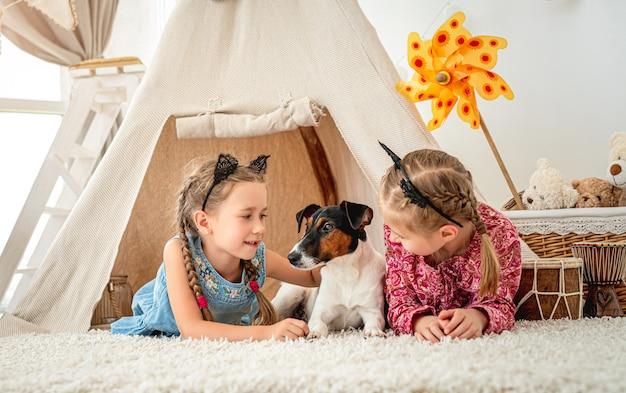 ウィグワムで犬と一緒に横になっている子供