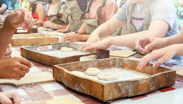 Дети лепят из теста пончики и раскладывают их на деревянных подносах. мастер-класс по выпечке.