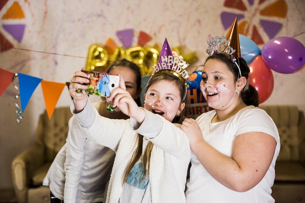 Children making funny selfie on smartphone