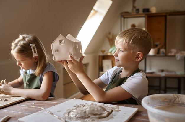 Дети лепят изделия из глины, малыши в мастерской. урок в художественной школе. юные мастера народных промыслов, приятное увлечение, счастливое детство