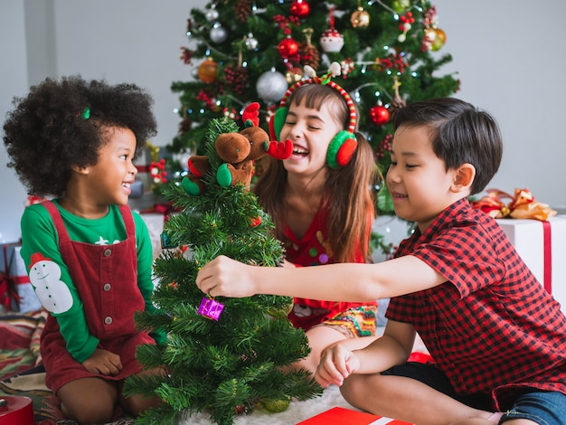 Children of many nationalities are celebrating christmas day, children under christmas tree with fun and happy