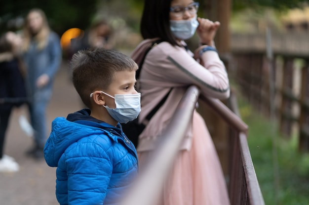 Children in masks look at animals through fence. boy and woman wearing warm clothes walking in zoo in autumn. quarantine concept.