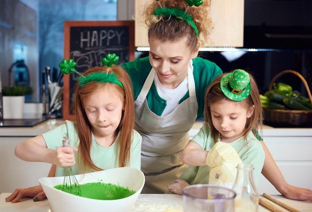 I bambini mescolano glassa fondente sotto la supervisione della madre