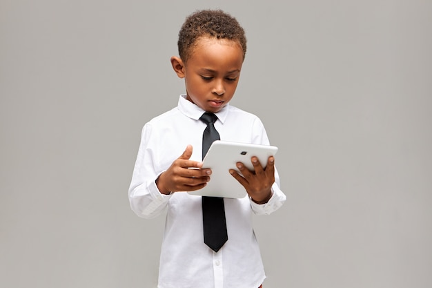 Children and modern technology concept. serious focused afro american schoolboy in uniform holding white generic digital tablet, playing online game or learning, having concentrated expression