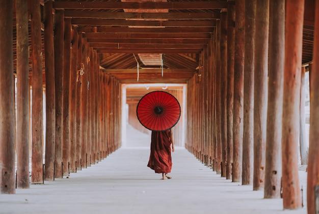 寺院に歩く子供僧侶。ミャンマーバガンの伝統的な衣装と傘を持つビルマ僧
