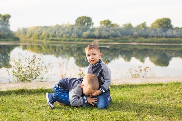 Children and nature concept. two brothers sitting on the grass over nature background