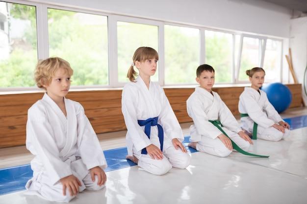 Дети у окна. дети в белом кимоно сидят у окна и слушают тренера