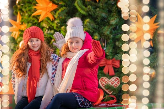 赤毛の姉妹の子供たちは、街のお祝いに飾られたクリスマスマーケットを歩きます。
