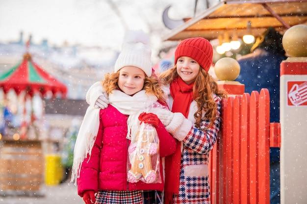 赤毛の姉妹の子供たちは、街のお祝いに飾られたクリスマスマーケットで、大きなジンジャーブレッドを手に持って歩きます。