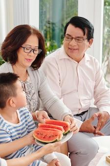 Дети предлагают бабушкам и дедушкам ломтики арбуза во время семейного ужина дома