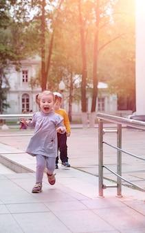 都市公園で春に散歩している子供たち。女の子は公園を歩いています。子供とお母さんが街を歩いています。