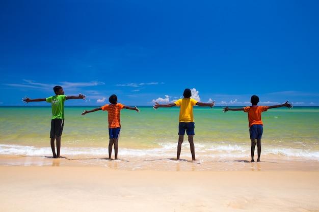 両手を広げてビーチで子供たち