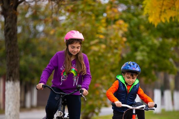 Дети на велосипедах и в защитных шлемах катаются в осеннем городском парке. на фото деревья сзади размыты.