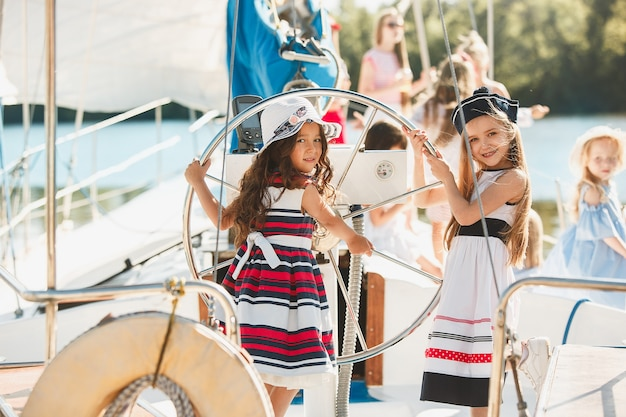 オレンジジュースを飲む海のヨットに乗っている子供たち。屋外の青い空に対して10代または子供の女の子。カラフルな服。キッズファッション、晴れた夏、川、休日のコンセプト。