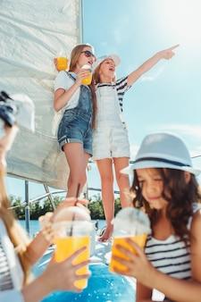 オレンジジュースを飲む海のヨットに乗っている子供たち。屋外の青い空に対して10代または子供の女の子。カラフルな服。