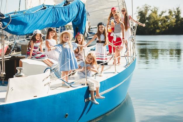 Дети на борту морской яхты пьют апельсиновый сок. девочки-подростки или дети против голубого неба на открытом воздухе. красочная одежда.