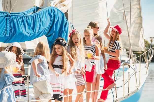 オレンジジュースを飲む海のヨットに乗っている子供たち。屋外の青い空に対して10代または子供の女の子