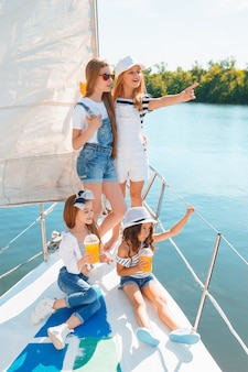 오렌지 주스를 마시는 바다 요트의 보드에 어린이