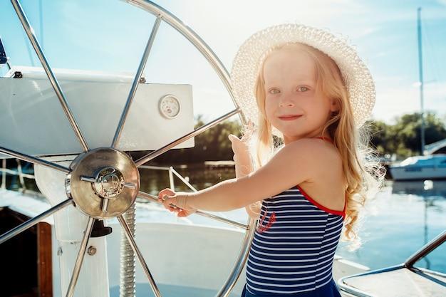 海のヨットに乗っている子供たち。屋外の青い空に対して10代または子供の女の子