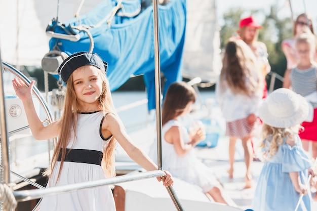 바다 요트의 보드에 아이들. 십대 또는 어린이 소녀 야외. 화려한 옷. 키즈 패션, 화창한 여름, 강 및 휴일 개념.