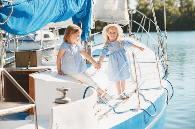 海のヨットに乗っている子供たち。 10代または子供の女の子の屋外。カラフルな服。
