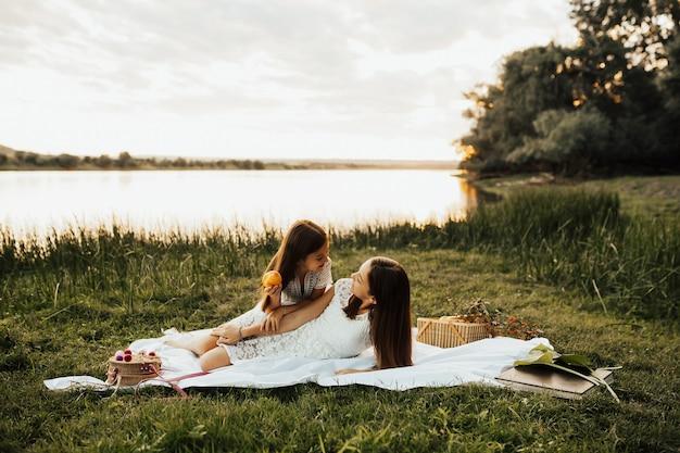 川の岸でピクニックをしている子供たち