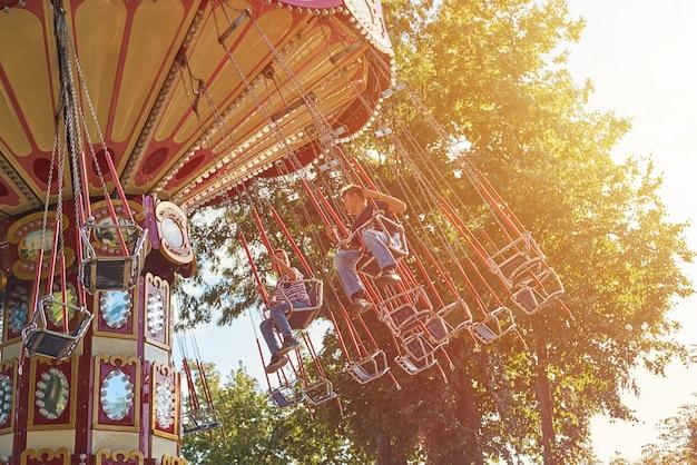遊園地のチェーンカルーセル上の子供