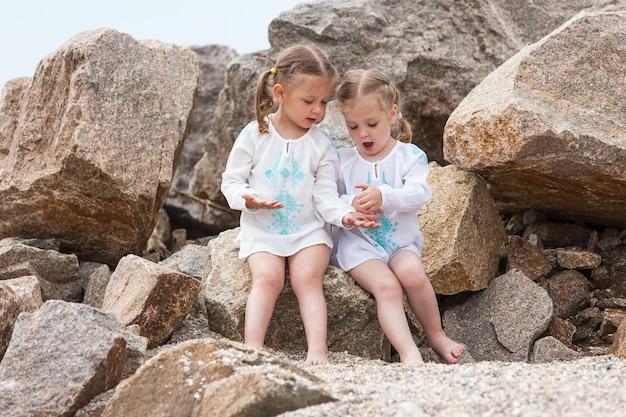 Дети на морском пляже. близнецы сидят на фоне камней и морской воды.