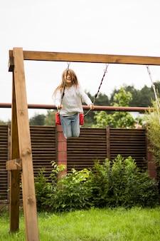 Дети на качелях. девушка качается на качелях во дворе. летнее веселье.