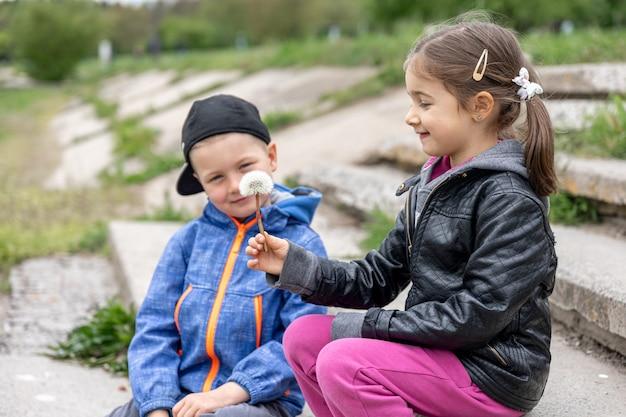 散歩中の子供たちはコミュニケーションを取り、花を見ます