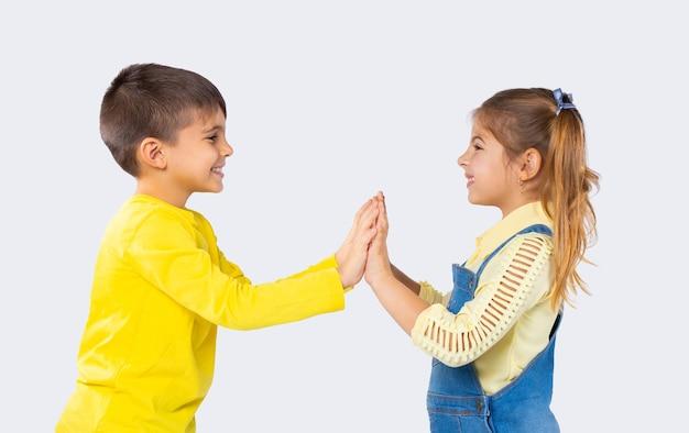 Дети на белом фоне мило улыбаются и смотрят друг на друга, играя в ручную игру