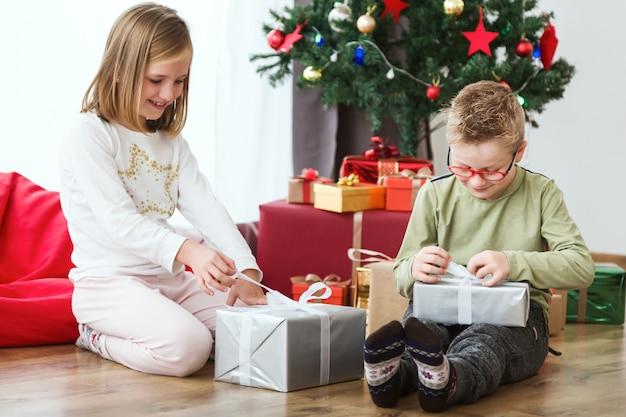 Bambini che aprono i regali di natale sul pavimento