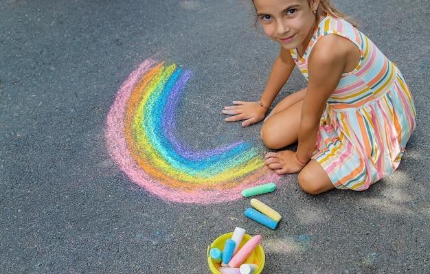 子供たちはアスファルトに虹を描きます。セレクティブフォーカス。キッズ。