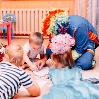 Children paint drow paper on floor with clown