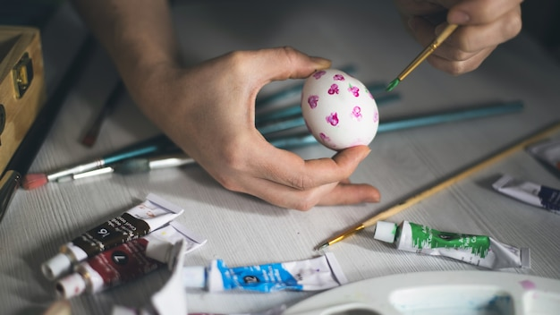 子供たちはアート材料でテーブルにイースターエッグを描く