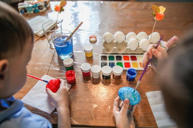 아이들은 부활절 테이블에 앉아 계란 페인트