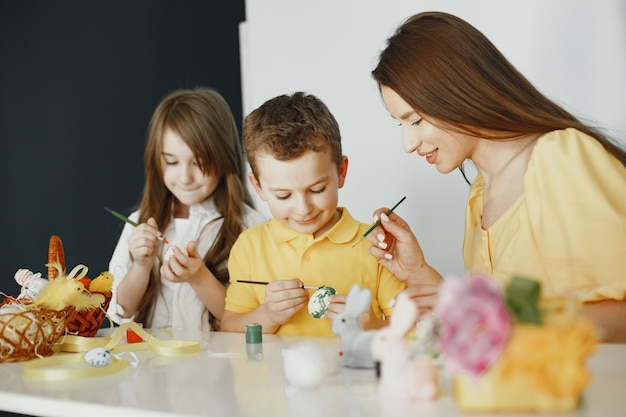 Дети раскрашивают яйца. мать учит детей. сидит за белым столом.