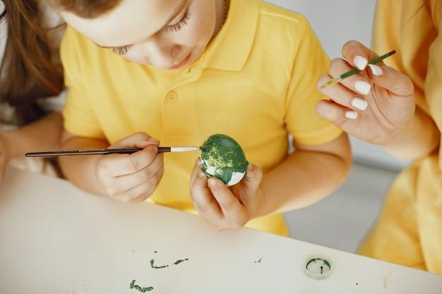 子供たちは卵を塗ります。母は子供たちに教えます。白いテーブルに座っています。
