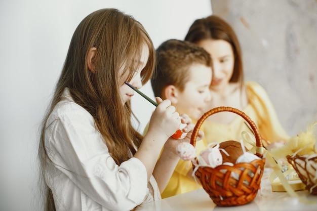 I bambini dipingono le uova. la madre insegna ai bambini. seduto a un tavolo bianco.